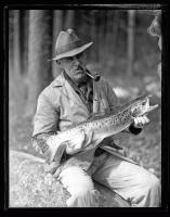 Man holding Landlocked Salmon, ca. 1935