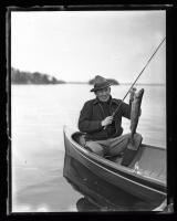 Man holding Landlocked Salmon, ca. 1935