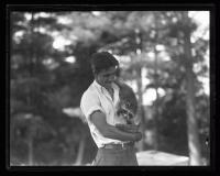 Man holding a raccoon, ca. 1935