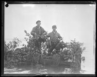 Two duck hunters in a camouflaged canoe, ca. 1935