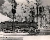 A locomotive steams past the old Colby campus, with Memorial Hall in the background.