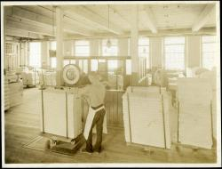 Weighing finished cloth at the Pepperell Mills, Biddeford, circa 1925