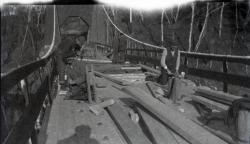 Workers repair damage to suspension bridge, Strong, 1915
