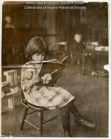 North School pupil reading, ca. 1910