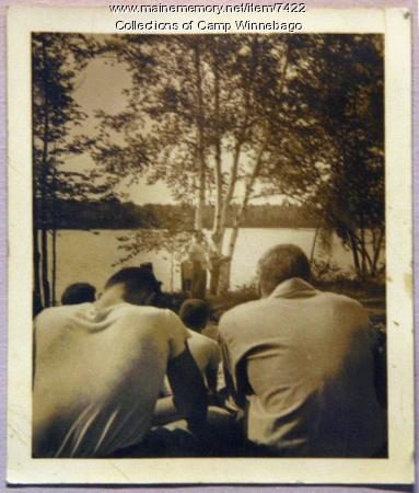 Counselors and campers around campfire, ca. 1950