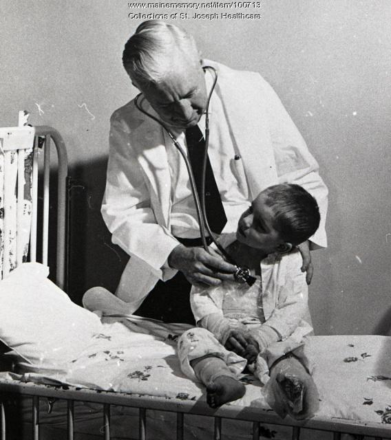 Doctor examining child patient at St. Joseph Hospital, Bangor, ca. 1960