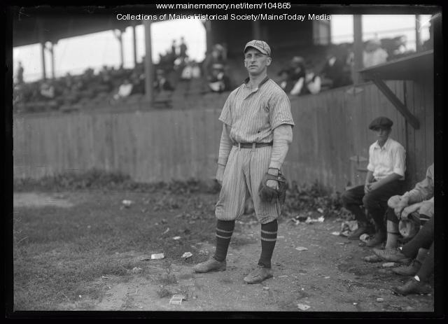 Baseball player standing in outfield of stadium, ca. 1920