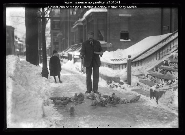 Man feeding pigeons, ca. 1920
