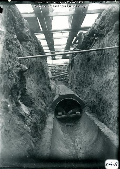 Man working inside a big sewer in Biddeford, 1914-1915