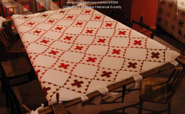Red and white quilt top on quilting frame
