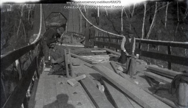 Workers repair damage to suspension bridge, Strong, 1915