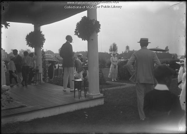 Men by porch survey a children's party at Biddeford Pool, 1917
