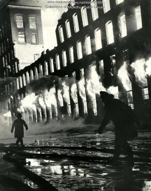 Flames rolling though the windows of Grafton Lumber, Biddeford, 1963
